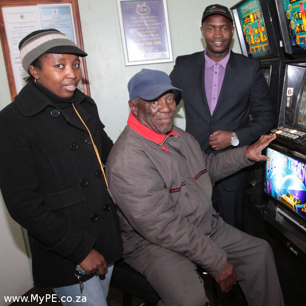 Mabutho Zwane (right), Eastern Cape Gambling and Betting Board CEO, watches avid punter Taroni Winston Mntu (centre), of Mdantsane, playing limited payout gambling machines at Vincent Tattersalls. Tattersalls teller Nomonde Masiko is (left) is ready to pay out the cash jackpot.