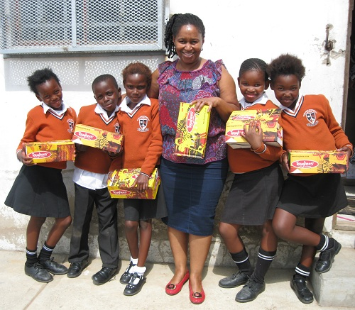 Rocklands Intermediate Farm School's foundation phase teacher Nothemba Msizi with some of the learners who received schools shoes from Sovereign Foods.