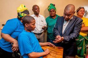 Minister of Transport, Dr. Blade Nzimande visiting road accident victim Jerome Peterson (seated) in Missionvale, Port Elizabeth.